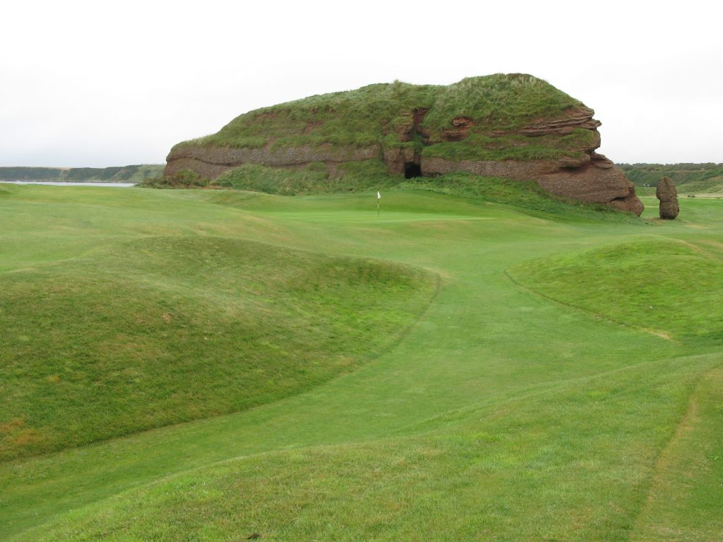 The 11th green at Cullen with the indomitable Boar Crag